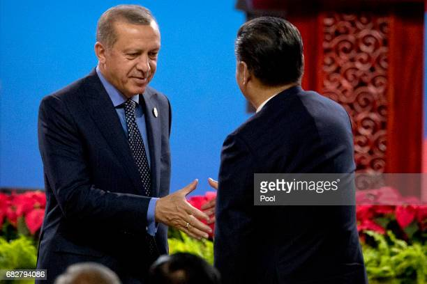 Turkey's President Recep Tayyip Erdogan left shakes hands with Chinese President Xi Jinping after Erdogan spoke during the opening ceremony of the...