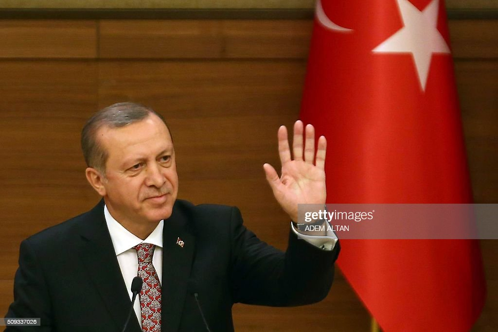 Turkey's President Recep Tayyip Erdogan waves as he delivers a speech during the monthly Mukhtars meeting (local administrators) at the Presidential Complex in Ankara on February 10, 2016. Turkish President Recep Tayyip Erdogan on February 10 accused the United States of creating a 'pool of blood' in the region by failing to recognise the main Syrian Kurdish organisations as terror groups. / AFP / ADEM ALTAN