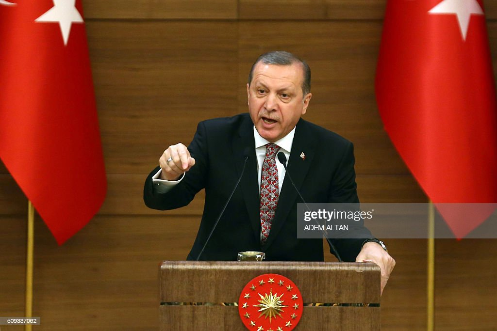 Turkey's President Recep Tayyip Erdogan waves delivers a speech during the monthly Mukhtars meeting (local administrators) at the Presidential Complex in Ankara on February 10, 2016. Turkish President Recep Tayyip Erdogan on February 10 accused the United States of creating a 'pool of blood' in the region by failing to recognise the main Syrian Kurdish organisations as terror groups. / AFP / ADEM ALTAN