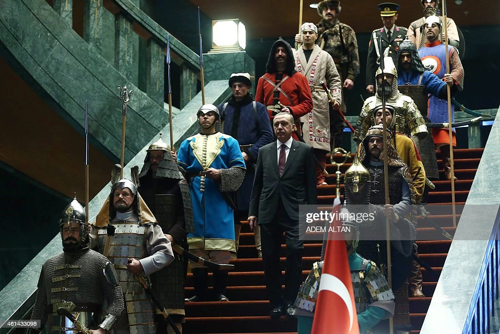 Turkey's President Tayyip Erdogan walks down the stairs in between soldiers wearing traditional army uniforms from the Ottoman Empire as he arrives...