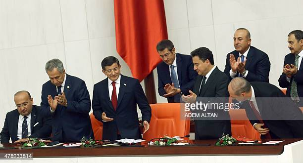 Turkey's Prime Minister Ahmet Davutoglu is applauded by deputies Prime ministers Yalcin Akdogan Bulent Arinc Ali Babacan and Numan Kurtulmus prior...