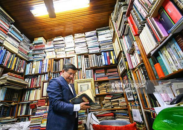 Turkey's Prime Minister and leader of the ruling Justice and Development Party Ahmet Davutoglu checks books at a secondhand bookseller in Istanbul...