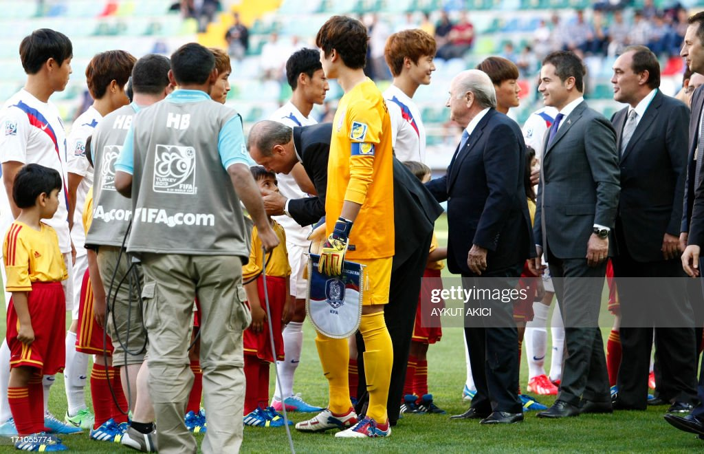 Turkey's prime minister Recep Tayyip Erdogan (C) and FIFA President Joseph Blatter (3rd R) shake hands with Korea Republic's football players during a group stage football match between Cuba and South Korea at the FIFA Under 20 World Cup at the Kadir Has stadium in Kayseri on June 21, 2013. AFP PHOTO/TURKPIX/Aykut AKICI