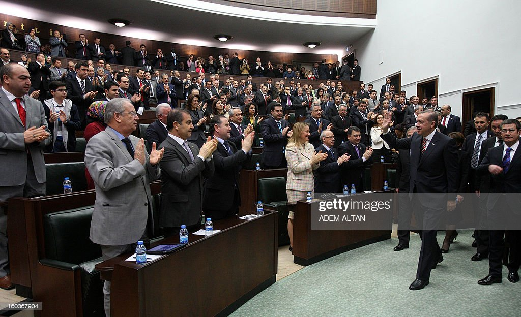 Turkey's Prime Minister Recep Tayyip Erdogan (R) is applauded by members of parliament after an address in Ankara on January 30, 2013. AFP PHOTO / ADEM ALTAN