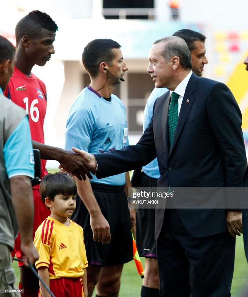 Turkey's prime minister Recep Tayyip Erdogan (R) shakes hands with a Cuban football player during a group stage football match between Cuba and South Korea at the FIFA Under 20 World Cup at the Kadir Has stadium in Kayseri on June 21, 2013. AFP PHOTO/TURKPIX/Aykut AKICI