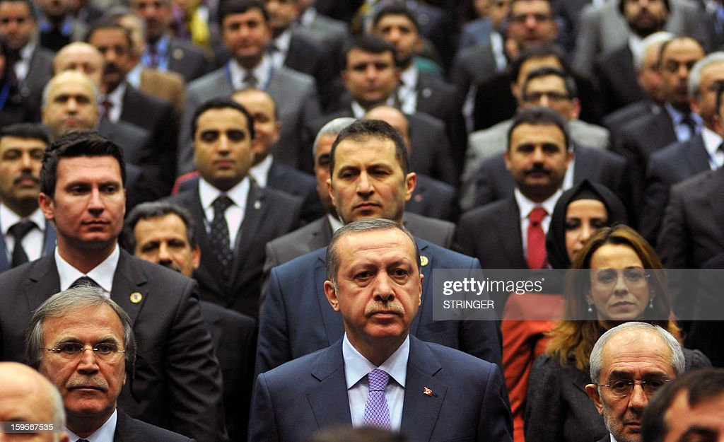 Turkey's Prime Minister Recep Tayyip Erdogan (C) stands amongst members of his ruling Justice and Development Party (AKP) at the party headquarters in Ankara on January 16, 2013. Turkey has sought information from France over the killing of three women Kurdish activists in Paris, a foreign ministry spokesman said January 15, 2013.