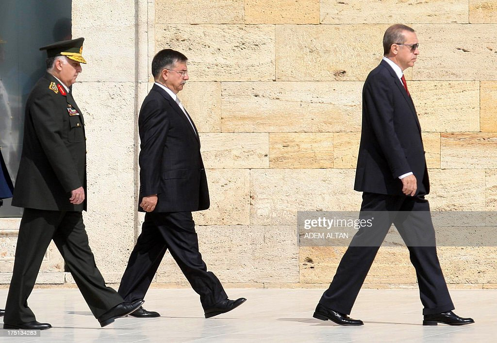 Turkey's Prime Minister Tayyip Erdogan (R) attends a wreath-laying ceremony, followed by Turkish National Defense Minister Ismet Yilmaz (C) and Chief of Staff General Necdet Ozel, at the mausoleum of modern Turkey's founder Mustafa Kemal Ataturk before a meeting of the High Military Council in Ankara on August 1, 2013.