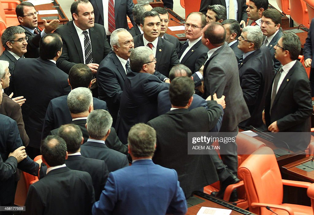 Turkey's ruling Ak Party lawmaker Omer Faruk Oz stands on a chair as members of parliament from the ruling AK Party and Republican People's Party get...