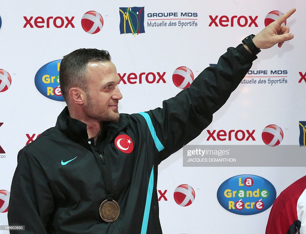 Turkey's Yavuz Karamollaoglu celebrates his bronze medal on the podium of the Male Kumite under 84kg category at the Karate world championships on November 24, 2012 in Paris.