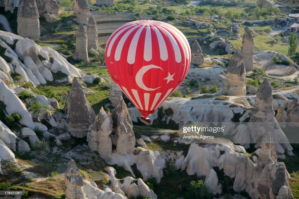 A Turkis-flagged hot air balloon the earth pillars on August 21, 2013 in Cappadocia, Turkey. Cappadocia, famous for its chimney rocks, hot air balloon trips, underground cities and boutique hotels carved into rocks, has received approximately 1.5 million national and international tourists in half a year, according to the statements released by the local governmental bodies. The historical region in Central Anatolia and one of the most popular tourism destinations in Turkey, offering attractions such as Goreme open-air museum, Kaymakli and Derinkuyu underground cities.