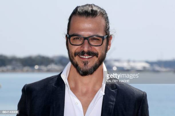 Turkish actor Mehmet Gunsur who stars in the series 'Phi' poses during a photocall as part of the MIPTV event on April 3 2017 in Cannes southeastern...