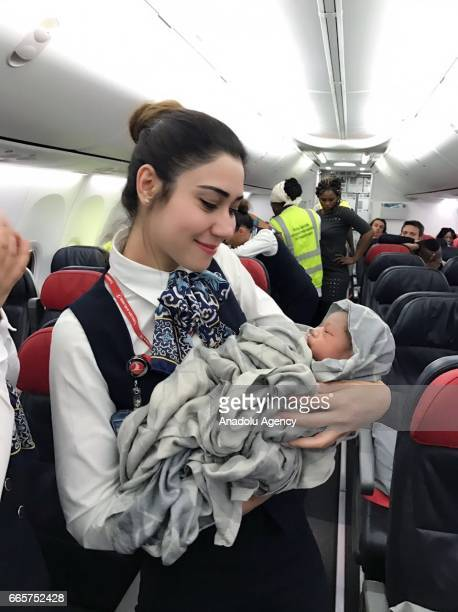 A Turkish Airlines hostess holds a baby born in a plane during a flight from Conakry to Ouagadougou to Istanbul on April 7 2017 in the air Cabin crew...