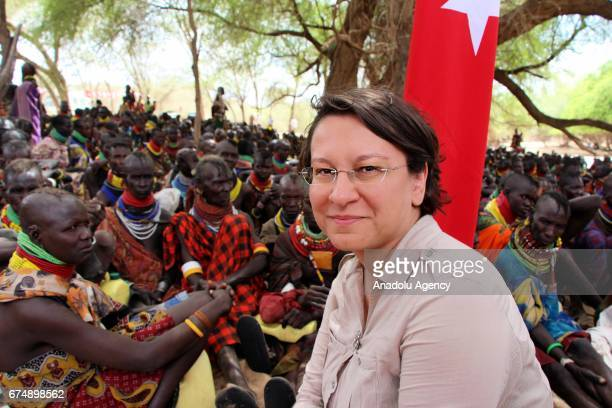 Turkish Ambassador to Kenya Deniz Eke sits in front of a Turkish flag with Kenyan people wearing traditional customes as they wait for an aid...