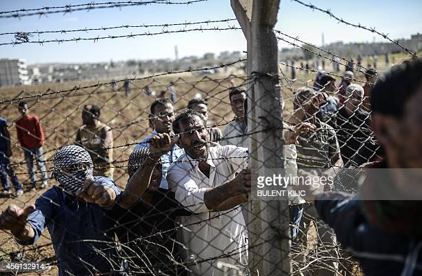 Turkish and Syrian Kurds try to tear down the border fences to cross into neighboring Syria during a demonstration near the Mursitpinar border...
