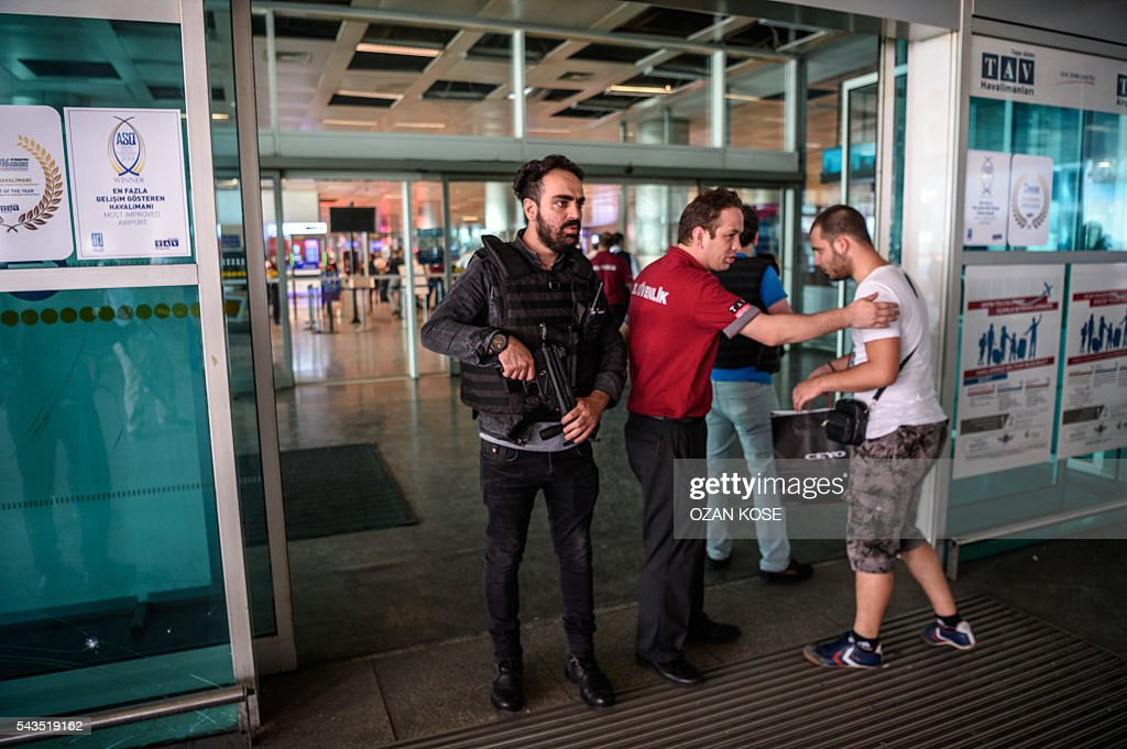 A Turkish anti riot police officer (L) and an employee of a private security company patrols (C) check as passengers enter the Ataturk airport International arrival terminal on June 29, 2016 a day after a suicide bombing and gun attack targeted Istanbul's airport, killing at least 36 people. A triple suicide bombing and gun attack that occurred on June 28, 2016 at Istanbul's Ataturk airport has killed at least 36 people, including foreigners, with Turkey's prime minister saying early signs pointed to an assault by the Islamic State group. / AFP / OZAN