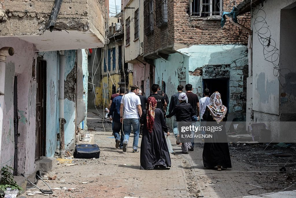 Turkish anti riot police officers accompany inhabitants to fetch belongings from their homes in the historical district in Diyarbakir, southeastern Turkey, on May 5, 2016. / AFP / ILYAS