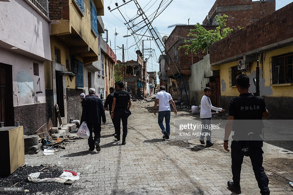 Turkish anti riot police officers accompany men to fetch belongings from their homes in the historical district in Diyarbakir, southeastern Turkey, on May 5, 2016. One Turkish soldier was killed and 20 others were wounded when a car bomb blamed on Kurdish militants exploded in the Kurdish-majority southeast, the army said on May 2, 2016. In a statement, the army said a total of 23 people were wounded in the blast which took place late on May 1, 20 of them soldiers and three of them civilian family members. The car bomb detonated near a military command complex in the Dicle district of the Kurdish majority province of Diyarbakir, a security source told AFP, blaming the attack on the outlawed Kurdistan Workers' Party (PKK). Turkey has been waging a major military offensive against the PKK, listed as a terror group by Ankara and much of the international community, after a two-year fragile ceasefire collapsed last summer. AKENGIN