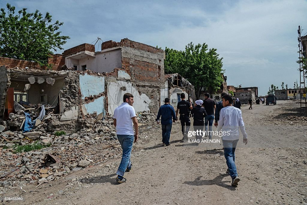 Turkish anti riot police officers accompany men to fetch belongings from their homes in the historical district in Diyarbakir, southeastern Turkey, on May 5, 2016. / AFP / ILYAS
