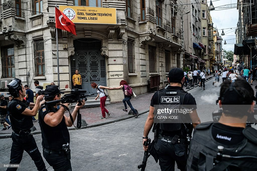 Turkish anti riot police officers fire rubber bullets to disperse demonstrators gathered for a rally staged by the LGBT community on Istiklal avenue in Istanbul on June 26, 2016. Riot police fired tear gas and rubber bullets to disperse protesters defying a ban on the city's Gay Pride parade. Authorities in Turkey's biggest city had banned the annual parade earlier this month citing security reasons, sparking anger from gay rights activists. KOSE