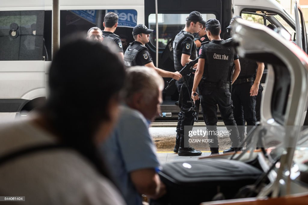 Turkish anti riot police officers prepare to stand guard as people walk nearby the explosion site at the Ataturk airport International terminal on July 1, 2016 three days after a suicide bombing and gun attack targeted Istanbul's Ataturk airport, killing 44 people. The suicide attackers who launched the deadly Istanbul airport assault were planning to take dozens of passengers hostage, Turkish media reported on July 1, 2016, as CCTV of the bombers' faces emerged. Turkish officials have pointed blame at the Islamic State jihadist group for June 28 night's gun and bomb spree at Ataturk airport, which left 44 people dead including 19 foreigners. KOSE