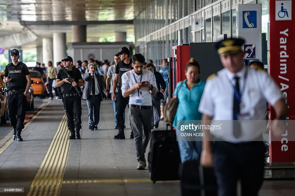 Turkish anti riot police officers stand guard as people walk nearby the explosion site at the Ataturk airport International terminal on July 1, 2016 three days after a suicide bombing and gun attack targeted Istanbul's Ataturk airport, killing 44 people. The suicide attackers who launched the deadly Istanbul airport assault were planning to take dozens of passengers hostage, Turkish media reported on July 1, 2016, as CCTV of the bombers' faces emerged. Turkish officials have pointed blame at the Islamic State jihadist group for June 28 night's gun and bomb spree at Ataturk airport, which left 44 people dead including 19 foreigners. KOSE