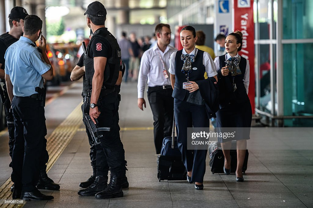Turkish anti riot police officers stand guard as stewardess walk nearby the explosion site at the Ataturk airport International terminal on July 1, 2016 three days after a suicide bombing and gun attack targeted Istanbul's Ataturk airport, killing 44 people. The suicide attackers who launched the deadly Istanbul airport assault were planning to take dozens of passengers hostage, Turkish media reported on July 1, 2016, as CCTV of the bombers' faces emerged. Turkish officials have pointed blame at the Islamic State jihadist group for June 28 night's gun and bomb spree at Ataturk airport, which left 44 people dead including 19 foreigners. KOSE