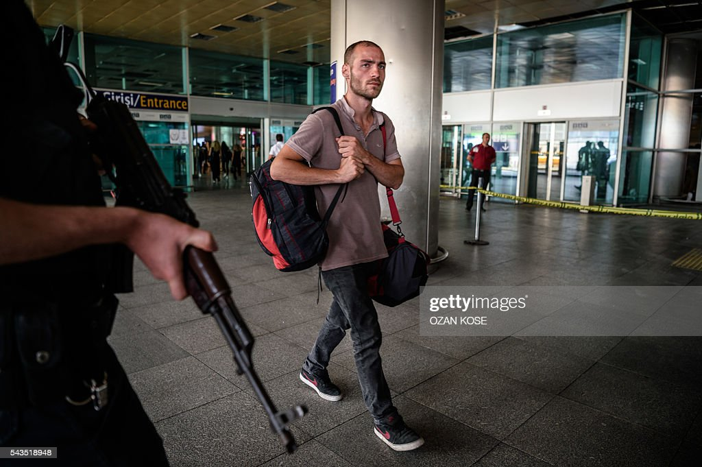 A Turkish anti-riot police officer (L) stands guard as a man walks past near the explosion site on June 29, 2016 at Ataturk airport International arrival terminal in Istanbul, a day after a suicide bombing and gun attack targeted Istanbul's airport, killing at least 36 people. A triple suicide bombing and gun attack that occurred on June 28, 2016 at Istanbul's Ataturk airport has killed at least 36 people, including foreigners, with Turkey's prime minister saying early signs pointed to an assault by the Islamic State group. / AFP / OZAN