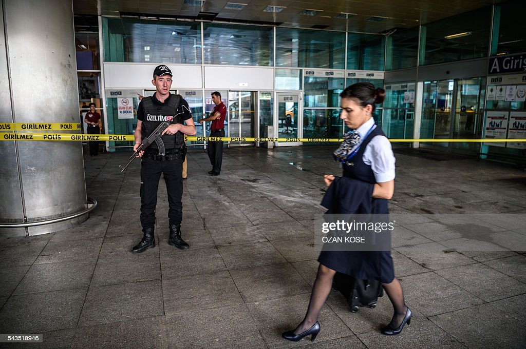 A Turkish anti-riot police officer (L) stands guard as a stewardess walks past near the explosion site on June 29, 2016 at Ataturk airport International arrival terminal in Istanbul, a day after a suicide bombing and gun attack targeted Istanbul's airport, killing at least 36 people. A triple suicide bombing and gun attack that occurred on June 28, 2016 at Istanbul's Ataturk airport has killed at least 36 people, including foreigners, with Turkey's prime minister saying early signs pointed to an assault by the Islamic State group. / AFP / OZAN