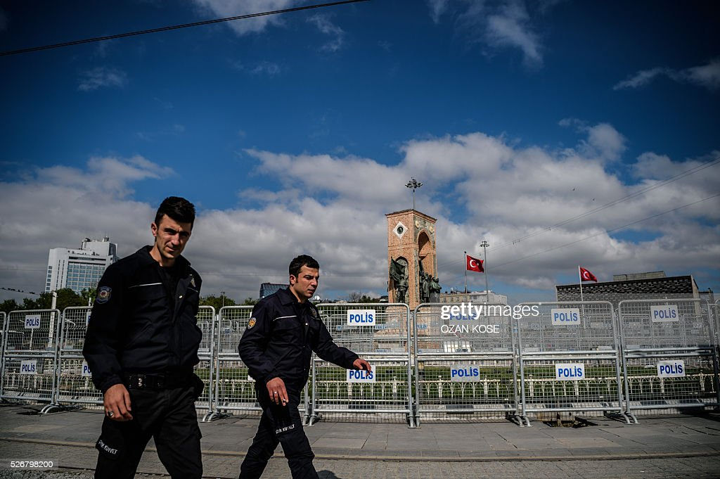 Turkish anti-riot police walk by fences during a May Day rally in Taksim square in Istanbul, on May 1, 2016. Turkish labour activists and leftists marked the annual May Day holiday, with thousands of security deployed and bracing for trouble after the authorities refused to allow protests in central Taksim Square. / AFP / OZAN