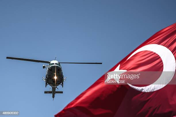 Turkish army helicopter flies behind a Turkish flag during a military parade marking the 93rd anniversary of Victory Day in Istanbul on August 30...