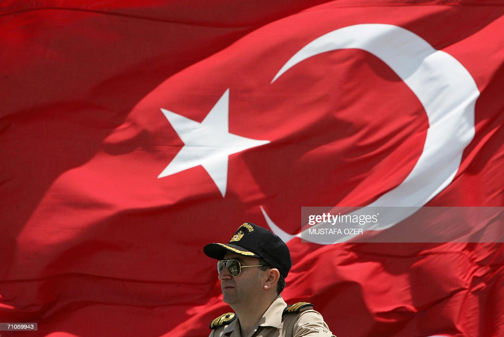 Turkish army officer stands in front of a Turkish flag at the TCG Barbaros Brigade during the Anatolian Sun06 military exercise in the Mediterranean...