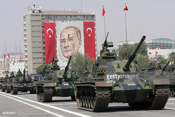 Turkish army tanks parade in front of a giant banner with a portrait of the founder of modern Turkey Mustafa Kemal Ataturk during Victory Day...