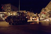 Turkish army vehicles drive in a street of the Syrian town of Kobane on February 21 during an operation to relieve the garrison guarding the Suleyman...