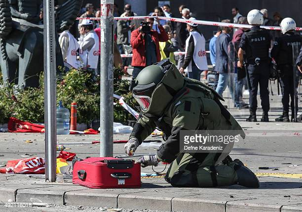 Turkish bomb expert investigates a suitcase at the blast scene after an explosion during a peace march in Ankara October 10 2015 in Ankara Turkey At...