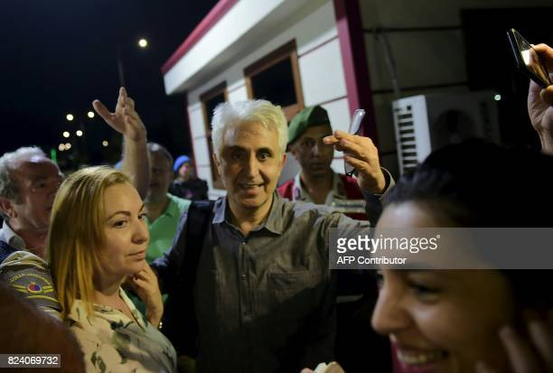 Turkish cartoonist Musa Kart of the Cumhuriyet is greeted by his wife after being freed from Silivri prison on July 28 2017 following a Turkish court...