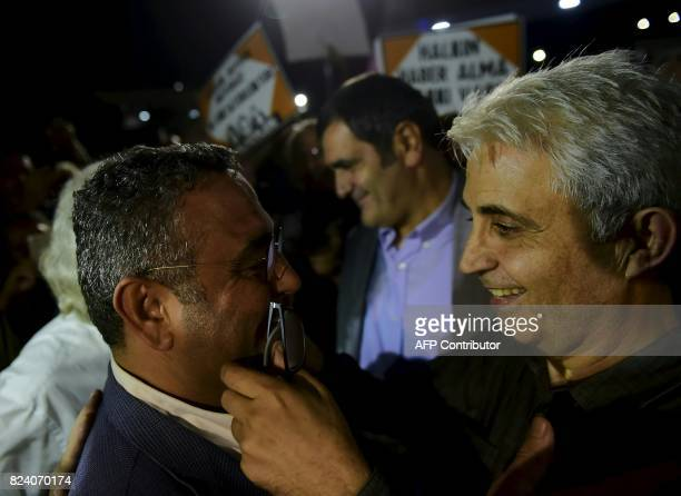 Turkish cartoonist Musa Kart of the Cumhuriyet newspaper is welcomed by the main opposition Republic People's Party MP Sezgin Tanrikulu after being...