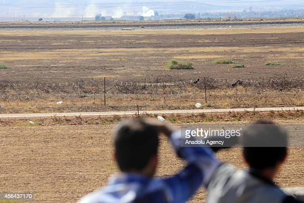 Turkish citizens watch the smoke that rises among the buildings following the shelling during clashes between Islamic State of Iraq and the Levant...