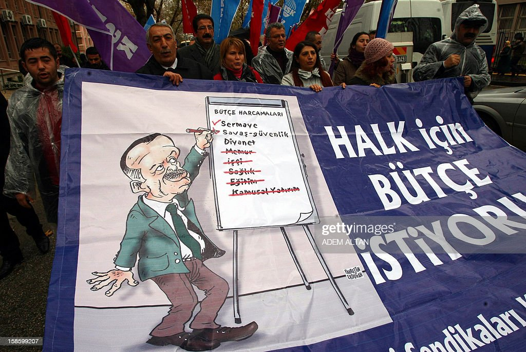 Turkish civil servants hold a banner, featuring budget cuts made a caricature of Prime Minister Recep Tayyip Erdogan, as they protest on December 20, 2012 outside the parliament in Ankara against the proposed 2013 government budget. The 10-day long budget debate at parliament opened on December 20.