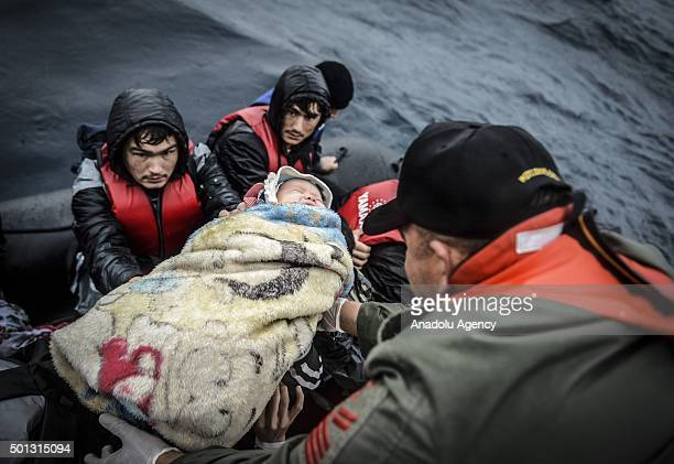 A Turkish coast guard pulls a refugee baby into the ship as he tries to rescue refugees who were illegally trying to reach Greece's Lesbos island...