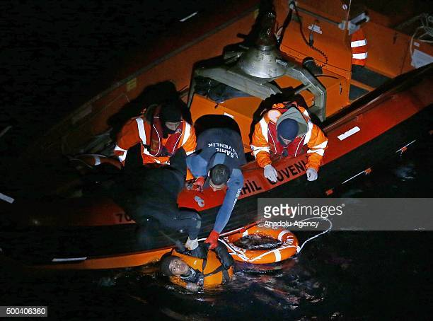 Turkish Coast Guard ship TCSG Umut crew members rescue the migrants after their boat sank off as they were trying to cross Aegean Sea near Izmr...