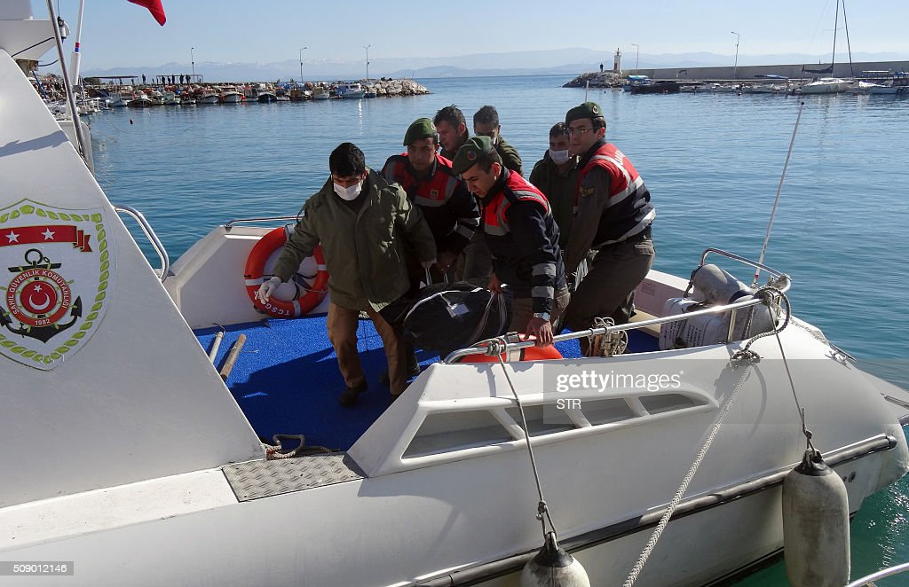 Turkish coast guards and rescuers carry the body of a drowned migrant off a rescue boat, on February 8, 2016 at Altinoluk district, in Balikesir. At least 35 migrants drowned in two accidents in the Aegean Sea on February 8, as they tried to cross from Turkey to Greece, Turkish media said. / AFP / STR
