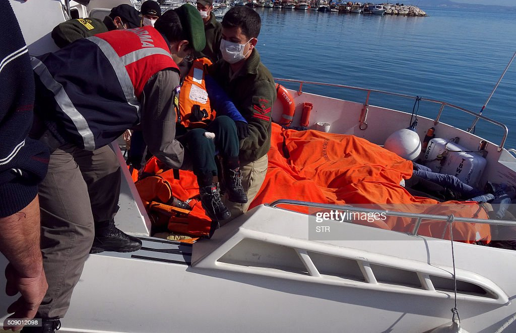 Turkish coast guards lift the the body of a child off a rescue boat, on February 8, 2016 at Altinoluk district, in Balikesir. At least 35 migrants drowned in two accidents in the Aegean Sea on February 8, as they tried to cross from Turkey to Greece, Turkish media said. / AFP / STR
