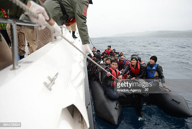 Turkish coast guards members are seen pulling a rope to rescue refugees who were illegally trying to reach Greece's Lesbos island through the Aegean...
