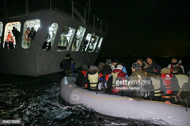 Turkish coast guards pull a refugee boat into a Turkish Coast Guard ship during a rescue operation for the asylum seeker refugees who were illegally...