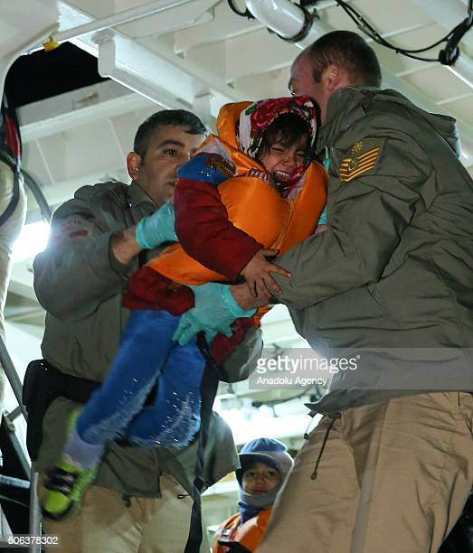 Turkish coast guards pull a refugee's child into a Turkish Coast Guard ship during a rescue operation for the asylum seeker refugees who were...