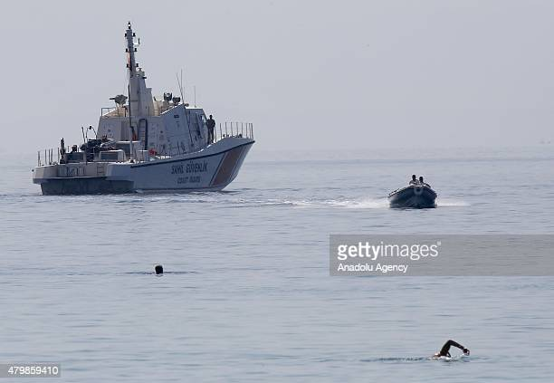 Turkish coastal guards carry the dead body of a female victim of a sank illegal immigrant boat as they arrive at the marina during a search and...