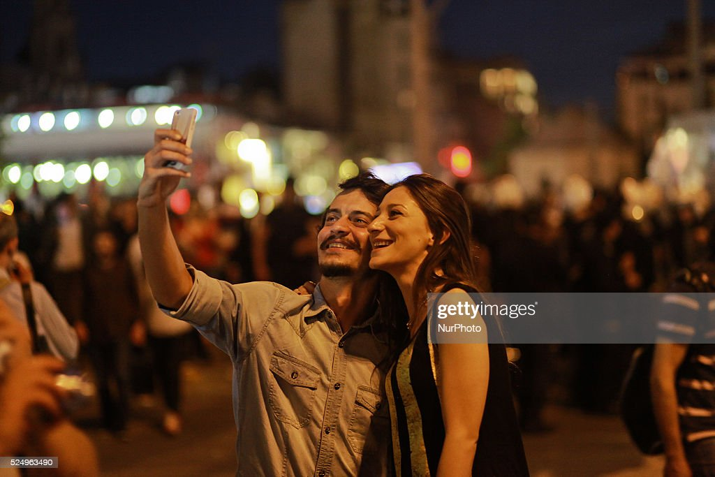 A Turkish couple takes a photo of themselves with the Turkish policemen in background at Taksim square during a protest against the mining disaster...