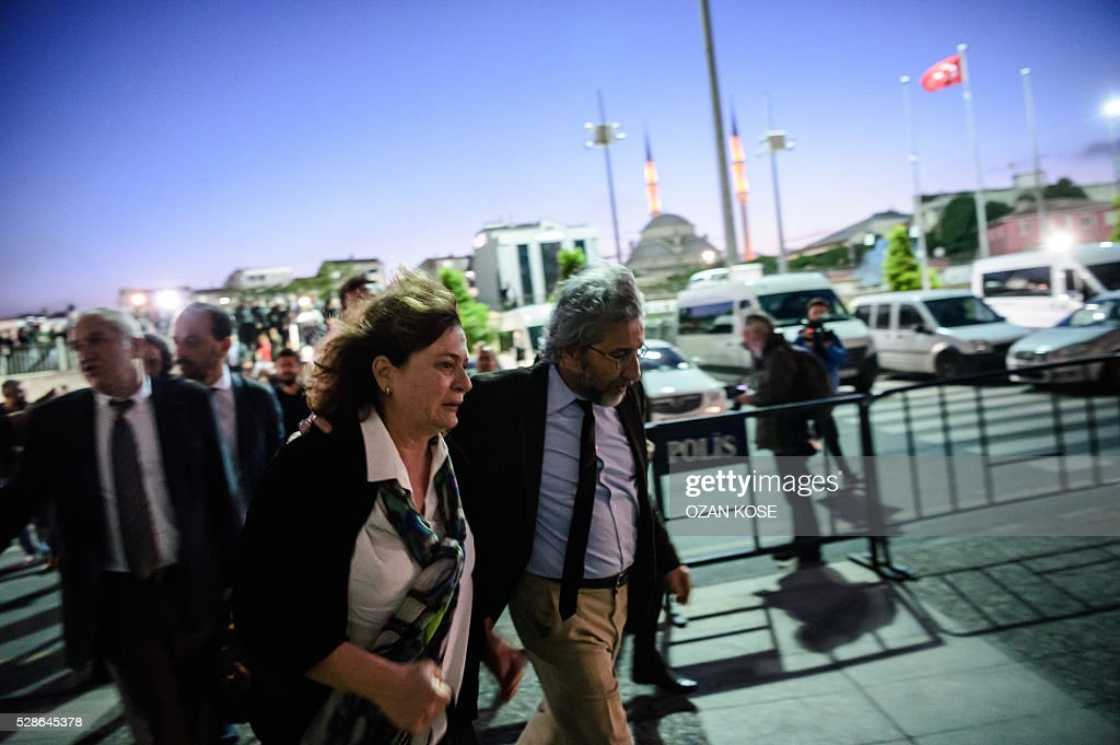 Turkish Cumhuriyet Daily newspaper Editor-in-chief Can Dundar (R) his wife Dilek Dundar leave the courthouse following his trial which ruled to jail him and a colleague on hugely controversial charges of revealing state secrets in a newspaper story, in Istanbul on May 6, 2016. Earlier in the day the opposition journalist Dundar escaped a shooting outside the courthouse where he was waiting during a break as the court prepared to deliver its verdict. The armed assailant was detained by the Turkish police. Dundar and the chief of the newspaper's bureau in Ankara Erdem Gul, will not immediately be placed in detention as the court of appeal has yet to rule on the case. / AFP / OZAN