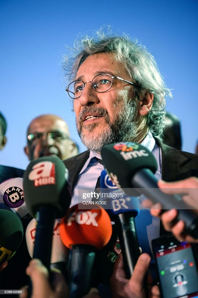 Turkish Cumhuriyet Daily newspaper Editor-in-chief Can Dundar speaks to the media following his trial which ruled to jail him and a colleague on hugely controversial charges of revealing state secrets in a newspaper story, in Istanbul on May 6, 2016. Earlier in the day the opposition journalist Dundar escaped a shooting outside the courthouse where he was waiting during a break as the court prepared to deliver its verdict. The armed assailant was detained by the Turkish police. Dundar and the chief of the newspaper's bureau in Ankara Erdem Gul, will not immediately be placed in detention as the court of appeal has yet to rule on the case. / AFP / OZAN