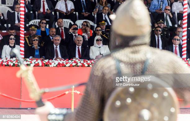 Turkish Cypriot leader Mustafa Akinci accompanied by Turkish Prime Minister Binali Yildirim look on towards a man dressed in chainmail and carrying a...